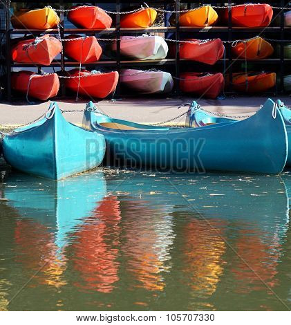 Bright Blue Canoes In Front of Red Kayaks
