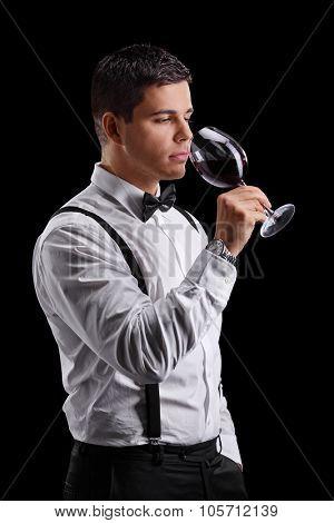 Vertical shot of an elegant young man tasting red wine on black background