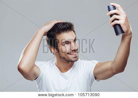 Young Man Applying Hair Spray To His Hair