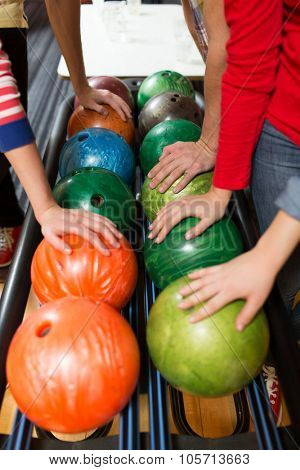 people, leisure, sport and entertainment concept - close up of players hands and ball return system in bowling club