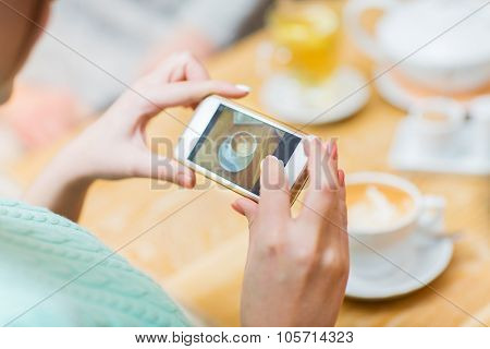 people, leisure, friendship and technology concept - close up of woman smartphone taking picture of coffee cup at caffee