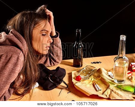 Girl in depression drinking alcohol and smokes cigarettes in solitude at the table.