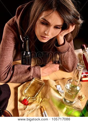 Girl in depression drinking alcohol and smokes cigarettes in solitude.