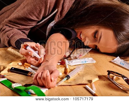 Female drug addict with  syringe on his arm lying at table.