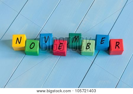 November wooden blocks with many-coloured pumpkins and decor against an old wood background. poster