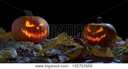 Creepy Two Pumpkins As Jack O Lantern Among Dried Leaves On Black