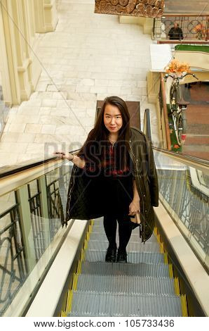Girl on escalator going up in parka poster