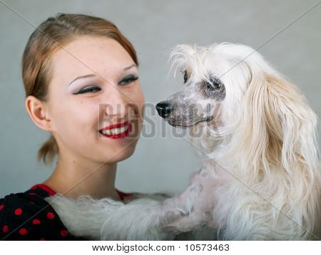 The beautiful smiling girl and chinese crested dog on grey background. Shallow DOF focus on dog poster