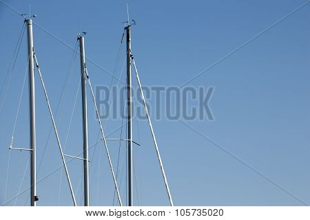 Sailing Boat Poles Against Blue Sky Background.