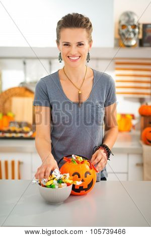Halloween candy is never too much! Smiling young woman in decorated kitchen preparing trick or treat candy for little robbers invasion. Traditional autumn holiday. poster