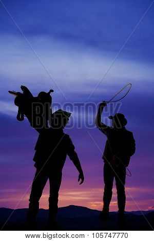 a silhouette of two cowboys one with a saddle and the other with a rope swinging above his head. poster