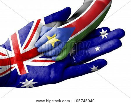 Adult Man Holding A Baby Hand With Australia And South Sudan Flags Overlaid. Isolated On White
