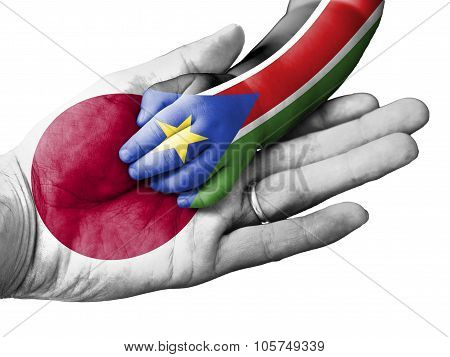Adult Man Holding A Baby Hand With Japan And South Sudan Flags Overlaid. Isolated On White