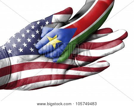Adult Man Holding A Baby Hand With United States And South Sudan Flags Overlaid. Isolated On White