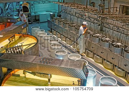 Worker Of The Cheese-making Factory Of Gruyeres Cleaning Cheese Molds
