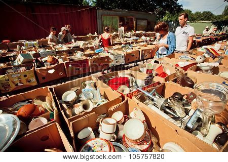 Vintage Cups, Plates And People Buying On Flea Market