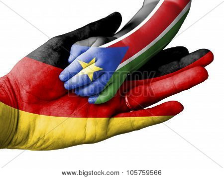 Adult Man Holding A Baby Hand With Germany And South Sudan Flags Overlaid. Isolated On White