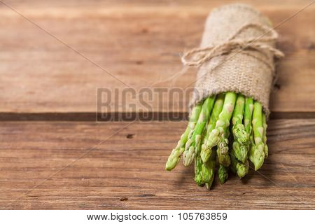 bunch of fresh asparagus stems on brown wooden table. poster
