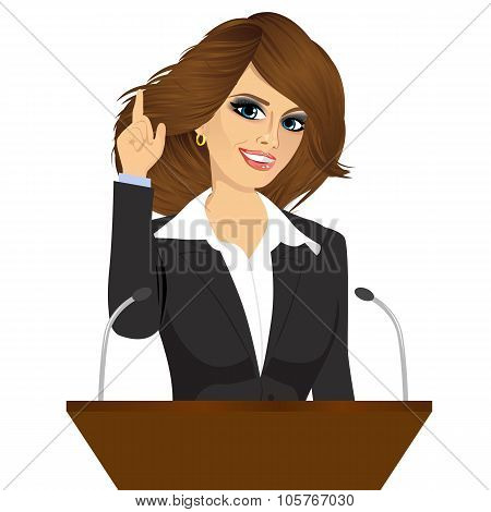 female orator standing behind a podium with microphones