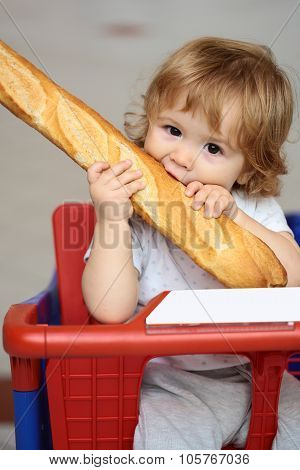 Kid Biting French Bread In Shopping Trolley