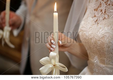 Beautiful bride in laced dress and groom holding burned candles decorated by white ribbon bow at wedding ceremony in church closeup indoor horizontal picture poster