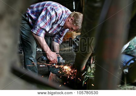 Farmer Repairing Lawn Mower In Wooden Barn, Sharpens Knives.