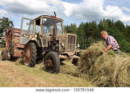 Harvest Time Hay, Russian Farmer Tractor-driver Working In Hayfield, Karelia.