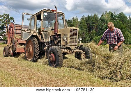 Farmers Field , Agronom Tractor-driver At Work Checking Fresh Hay.