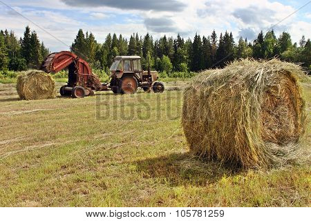 Farmer Tractor With Baler Spitting Out Round Rolls Of Hay.