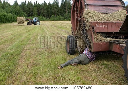 Time To Hay, Driver Mechanic Repairing Roll Baler In Field.