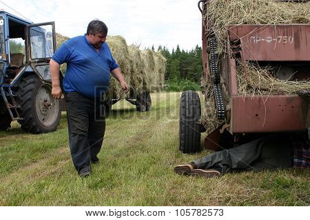 Farmer Repairing Tractor In Field, During Hay.