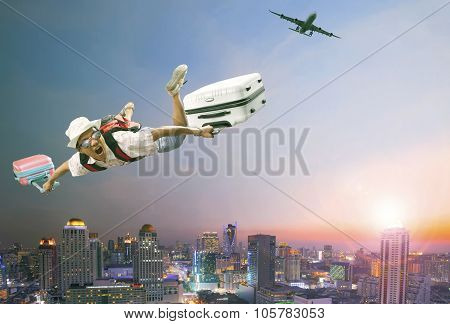 Younger Man Flying Mid Air With Belonging Luggage And Passenger Plane Over Beautiful Scenic Of Sky S