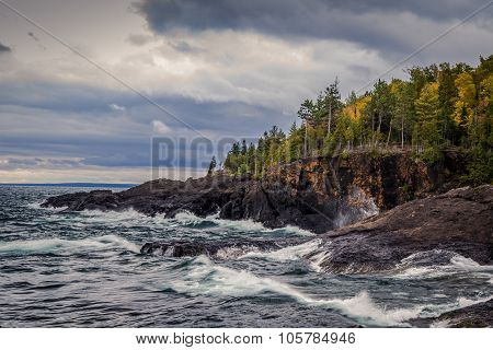 Gray sky and stormy seas crash on the cliffs of the black rocks along the shores of the Lake Superior coast. Presque Isle Park. Marquette, Michigan. poster