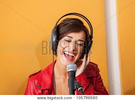Portrait of joyful young woman singing in recording studio poster