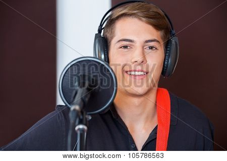 Portrait of handsome male singer smiling while wearing headphones in recording studio poster