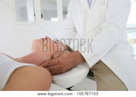 Chiropractor touching woman's head