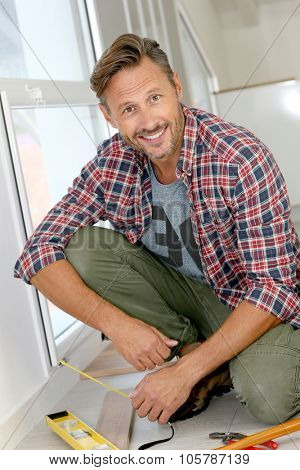Cheerful man at home installing new wooden floor