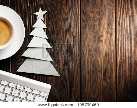 Christmas card. Keyboard, cup of coffee and Christmas tree made of paper on a wooden background
