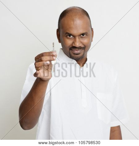 Portrait of Indian man holding new house key, real estate property agent concept, standing on plain background with shadow.