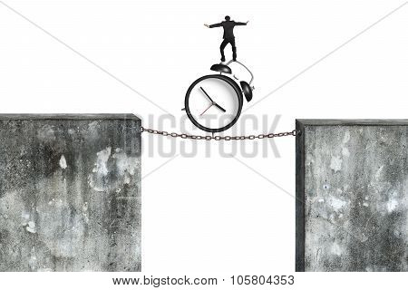 Businessman Balancing Alarm Clock On Rusty Chain Connected Concrete Walls