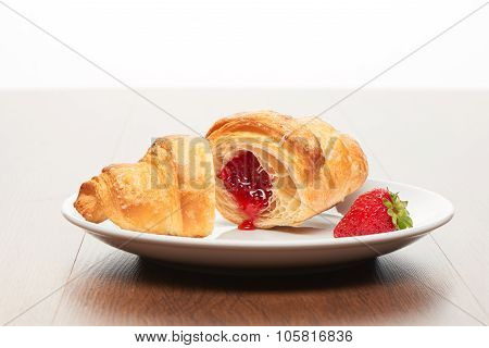 Fresh french croissant with strawberry jam filling cut into two pieces and strawberry on white ceram