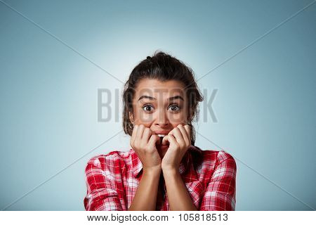 Close-up Portrait Of A Young Woman Scared ,afraid And Anxious Biting Her Finger Nails, Looking At Ca