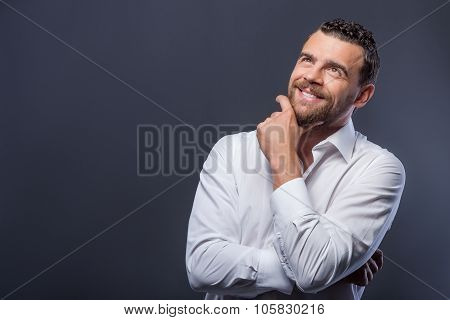 Cheerful young guy is dreaming with happiness