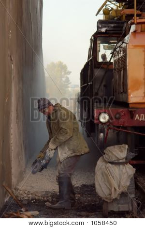 A Worker With A Hand-Held Grinding Tool In The Cloud Of Dust