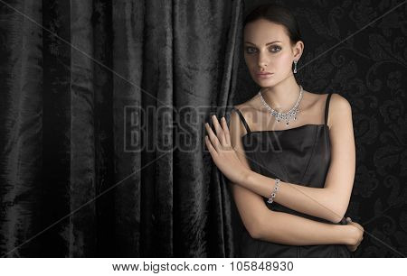 Beautiful woman with luxury jewellery on dark background