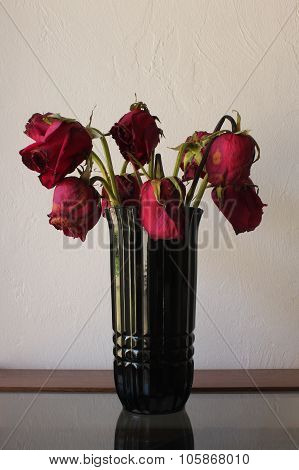 Sad,wilted red roses in black vase