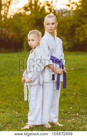 girls in white kimono during training karate exercises at summer outdoors