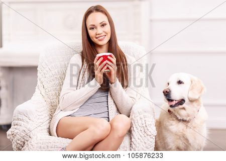 Pretty girl in the armchair with her pet around.