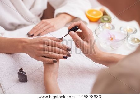 Process of painting fingernails at beauty salon