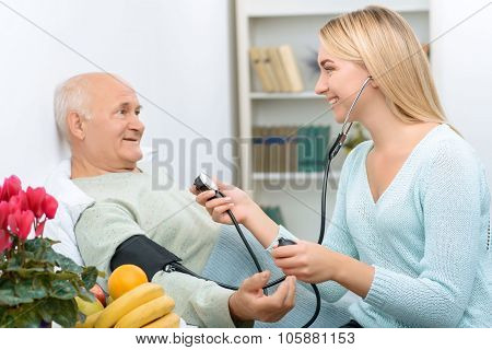 Young visiting relative measures blood pressure of the patient.